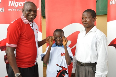 (L-r): Akinsola Omoniyi, area business manager, Airtel Nigeria, Lagos North,   a primary six pupil of St. John's Primary School with Mr. Adewale Oladele, the head teacher, during the presentation of eye glasses to pupils of the school in Oke-Agbo, Ijebu-Igbo, Ogun State